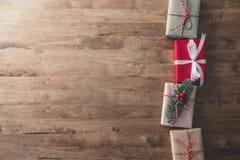 Cajas de regalo de vacaciones de la Navidad en la tabla de madera, fondo del diseño de la frontera Fotos de archivo