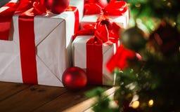 Cajas de regalo y bolas rojas debajo del árbol de navidad Imagenes de archivo