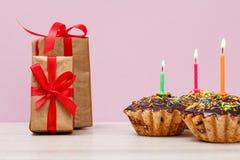 Cajas de regalo y magdalenas del cumpleaños con la quema de velas festivas en fondo de la lila imagen de archivo