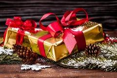 Cajas de regalos con las ramas del abeto en cierre de madera del fondo para arriba Foto de archivo