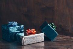 Cajas del día de fiesta con los arcos en una tabla de madera Foco selectivo Foto de archivo libre de regalías