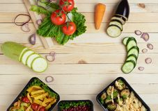 Cajas del envase de comida con la comida lista a comer, verduras crudas, zuchini y berenjenas, zanahoria y cebolla, lugar para el foto de archivo