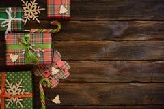 Cajas del regalo de Navidad adornadas con el documento colorido sobre de madera Imagenes de archivo