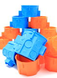 Cajas eléctricas azules y anaranjadas en el fondo blanco Fotografía de archivo libre de regalías