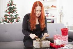 Cajas felices del regalo de Navidad del abrigo de la muchacha Foto de archivo libre de regalías
