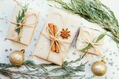 Cajas festivas como regalo de Navidad con el arco de la cinta y rama de árbol de abeto en el fondo blanco Foto de archivo
