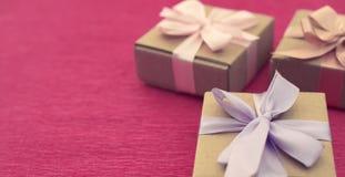 Cajas festivas de Kraft de la composición tres de la bandera con los regalos en fondo rosado brillante Imagen de archivo
