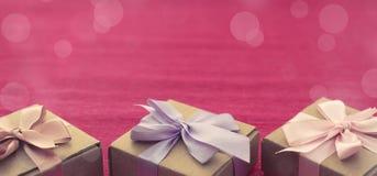 Cajas festivas de Kraft de la composición tres de la bandera con los regalos en fondo rosado brillante Imágenes de archivo libres de regalías