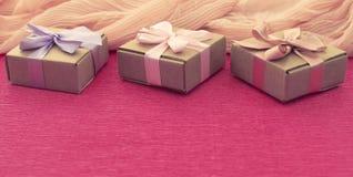 Cajas festivas de Kraft de la composición tres de la bandera con los regalos en fondo rosado brillante Foto de archivo libre de regalías