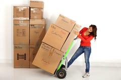 Cajas móviles de la mujer joven con con un camión o un carro de mano Foto de archivo libre de regalías