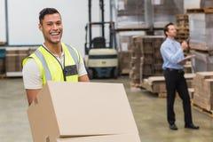 Cajas móviles sonrientes del trabajador del almacén en la carretilla Foto de archivo