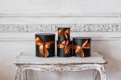 Cajas negras envueltas del regalo con las cintas como los regalos de Navidad en una pared blanca de lujo de la tabla diseñan el e Fotografía de archivo libre de regalías