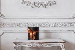 Cajas negras envueltas del regalo con las cintas como los regalos de Navidad en una pared blanca de lujo de la tabla diseñan el e Fotografía de archivo