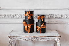 Cajas negras envueltas del regalo con las cintas como los regalos de Navidad en una pared blanca de lujo de la tabla diseñan el e Foto de archivo libre de regalías