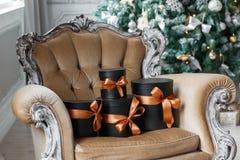 Cajas negras envueltas del regalo con las cintas como regalos de Navidad en una silla Imagen de archivo libre de regalías