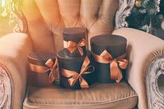 Cajas negras envueltas del regalo con las cintas como regalos de Navidad en una silla Fotos de archivo libres de regalías