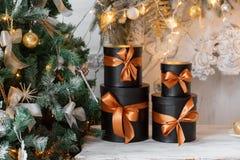 Cajas negras envueltas del regalo con las cintas como regalos de Navidad en una tabla Imagenes de archivo