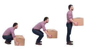 Cajas pesadas apropiadas que levantan contra dolor de espalda Foto de archivo libre de regalías