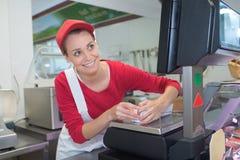 Cajero femenino en el carnicero del escritorio de las ventas Foto de archivo libre de regalías