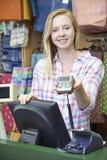 Cajero femenino At Sales Desk con la máquina de la tarjeta de crédito Imágenes de archivo libres de regalías