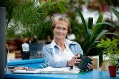Cajero mayor de la mujer en centro de jardinería fotos de archivo libres de regalías
