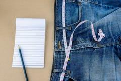 Cajgi i pomiarowa taśma, notepad, ołówek na drewnianym stole Zdjęcie Royalty Free