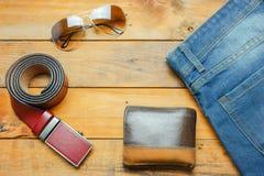 Cajgi, okulary przeciwsłoneczni i rzemiennego paska portfel na drewnianym roczniku, Obraz Royalty Free