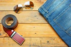 Cajgi, okulary przeciwsłoneczni i rzemienny pasek na drewnianym roczniku, Zdjęcie Royalty Free