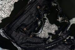 Cajgu błękitny ciemny namok w gąbki domyciu i moczy w gąbki wody czarnych, Barwionych cajgach brudnych, odziewa obraz royalty free