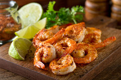 Cajun Shrimp. Delicious sauteed shrimp with cajun seasoning and lime on a maple plank Stock Image