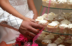 Cake 01. Fancy dressed couple, reaching for cupcakes Royalty Free Stock Image