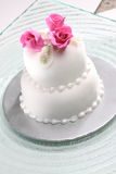 Cake. Garnished white satin cake, pure white color, with roses decoration on top. Melted glass plate base Stock Photos