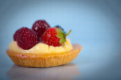 Cake. Pastry with vanilla and wildberries on blue background Stock Photography