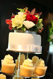 Cake. White wedding cake with roses on top and cupcakes underneath Stock Photo