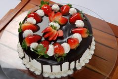 Cake. Covered with chocolate and strawberries Royalty Free Stock Image