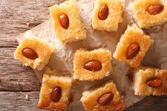 Cake with almonds basbousa close-up on paper. Horizontal top vie Stock Image