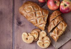 Cake with Apple filling and pastry in the shape of a heart with red apples on wooden table royalty free stock photography