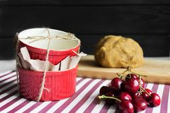 Cake baking forms and cherry. Cake baking forms and ingredients for a sweet cherry pie on a dark background royalty free stock images