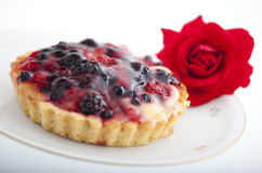 Cake with berries. A delicious cake with berries arranged on a plate with a roses next to it Royalty Free Stock Photo