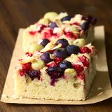 Cake with Berries and Coconut Flakes. Homemade cake with gooseberry, blueberry, redcurrant and coconut flakes, photographed on dark wood with natural light royalty free stock photos