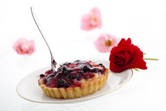Cake with berries surrounded by roses isolated. A delicious cake with berries arranged on a plate and surrounded by roses Stock Photo