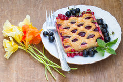 Cake with berry jam is served with fresh  red and black currant Stock Photo