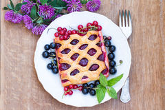 The cake with berry jam is served with red and black currants. R Stock Photography