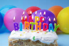 Cake with birthday greetings from burning candles on a colored background. Cake with birthday greetings from burning candles on a colored balloons background royalty free stock images
