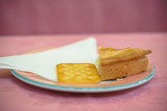 Cake and biscuit. Biscuit and cake on a plate with a paper napking and a pink tablecloth Royalty Free Stock Images