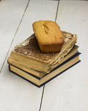 Cake and books. Cake and old books on a wooden background Royalty Free Stock Images