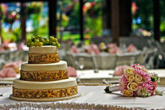 Cake and bouquet. A wedding cake next to a bouquet Stock Images