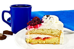 Cake in a bowl with coffee and chocolate. A piece of cake with white cream and red jelly on the plate, blue coffee mug with two pieces of chocolate, blue napkin Royalty Free Stock Photos