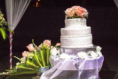 A cake and a brunch of orange roses on it and other roses next to the cake Stock Image