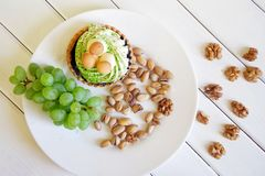 Cake, a bunch of grapes, pistachios and walnuts on white boards. Country breakfast royalty free stock image